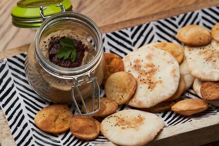 Homemade chicken liver pate in the jar on a wooden table, close-up. Chicken liver pate with crackers for Easter Stock Photo