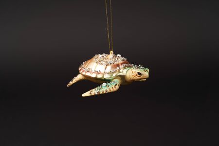 Turtle Christmas tree toy on dark background with copy space. Tortoise New Year tree decoration toy, close-up