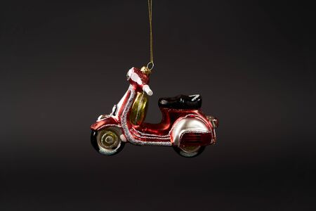 Scooter Christmas tree toy on dark background. Scooter New Year tree decoration toy, close-up Stock fotó