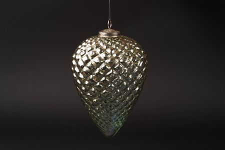 Fir cone Christmas tree toy on dark background. Pine cone New Year tree decoration toy, close-up