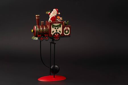 Santa on a steam train Christmas tree toy on dark background. New Year tree decoration toy, close-up