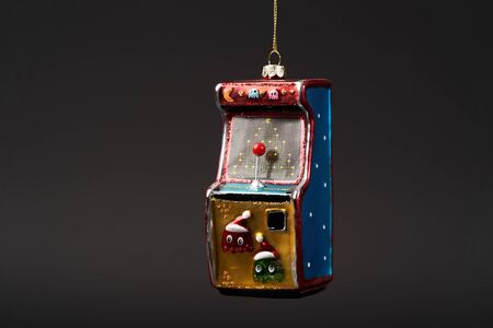 Arcade game machine Christmas tree toy on dark background with copy space. Arcade machine New Year tree decoration toy, close-up Stock fotó