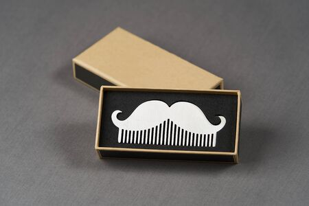 Silver mustache brush in gift box on grey background with copy space, close-up