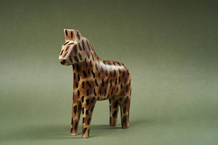 Wood horse toy on green background with copy space, close-up