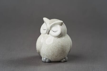 White owl toy over grey background with copy space, close-up
