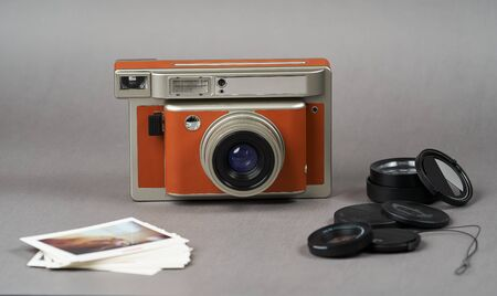 Retro camera and old photo film rolls on gray background with copy space, close-up