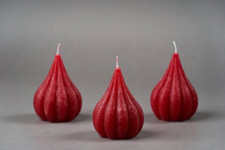 Three red fig candle over grey background, close-up Stock fotó