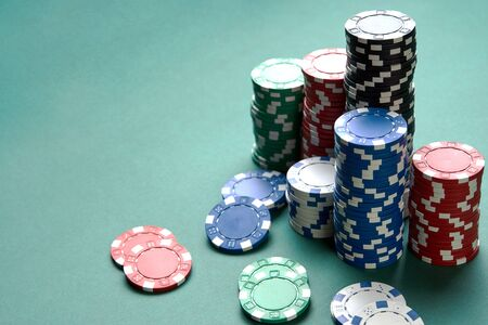 Poker gambling chips on green background with copy space. Casino poker bet, close-up
