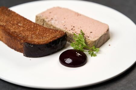 Chicken liver pate with blackcurrant and fig sauce. Toasted bread with pate in white plate on dark background with copy space, close-up. Chef's signature dish, luxury gastro cafe menu food