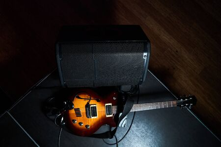 Yellow electric guitar and black amplifier on a dark background. Indoor concert stage with guitar and combo amplifier, close-up Reklamní fotografie