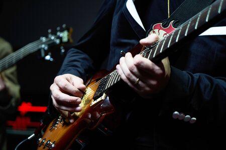 Gitarist handen speelt gitaarsolo, close-up. Gitarist met elektrische gitaar op het podium. Een zanger die gitaar speelt.