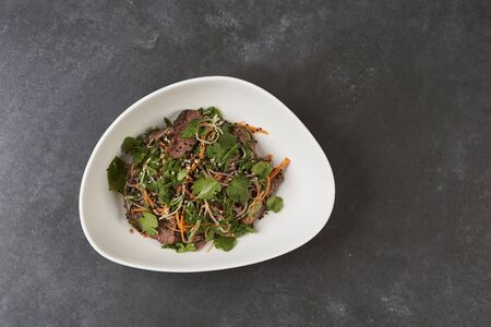 Thai style warm soba salad in white bowl on gray table background with copy space, close up