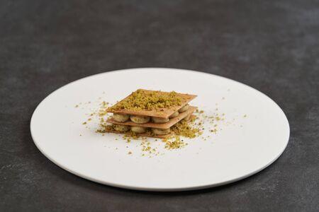 Pistachio baklava. Traditional Turkish Pistachio baklava on white plate on gray