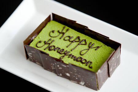 Happy honeymoon cake piece, close-up. Honeymoon cake on a white plate Zdjęcie Seryjne