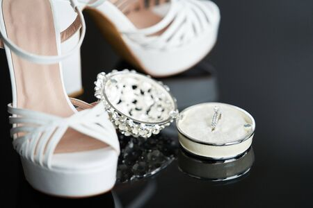 Bride Wedding accessories. Bride wedding set with shoes and engagement rings, close-up.