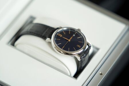 Silver Wrist watch with black leather belt, close-up. Luxury mechanical classic mens watch in gift box