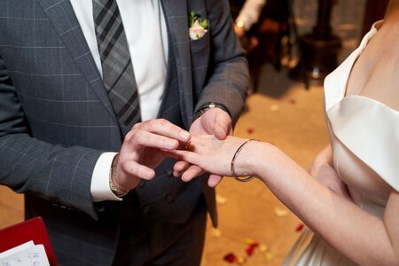 Groom Dresses the Ring for the Bride, close-up. Newlyweds exchange rings, groom puts the ring on the brides hand in marriage registry office