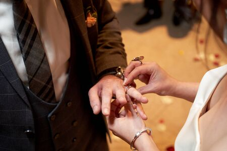 Bride Dresses the Ring for the Groom, close-up. Newlyweds exchange rings, bride puts the ring on the grooms hand in marriage registry office