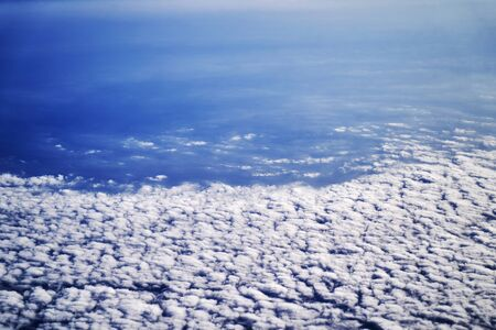 Airplane flying above clouds. Aircraft flying in the blue sky. View from airplane window engine and wing flying above the clouds