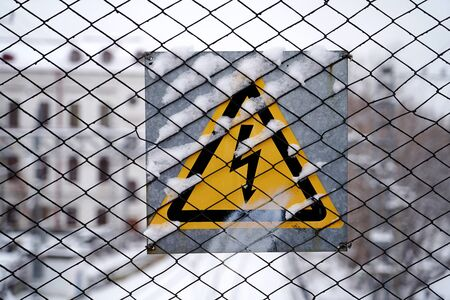 High voltage warning sign on wire mesh. Triangle High Voltage Danger Sign on metal fence. close-up.