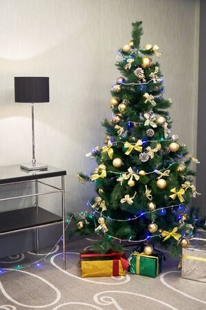Christmas tree and christmas gifts. Christmas gift boxes on floor near xmas tree in room Reklamní fotografie