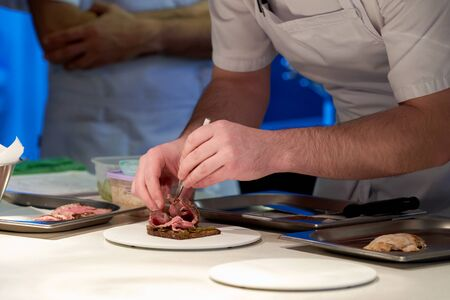 Chef Works in a Restaurant Kitchen. The chef in a white apron prepares the dish, close-up