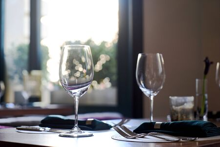 Restaurant table setting with Empty clean glasses. Banquet dining table serving with dishes, wine glasses, napkins