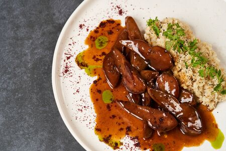 Baked lamb tongues with spicy bulgur porridge in a white plate on grey background with copy space, close-up Reklamní fotografie - 138101779