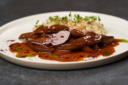 Baked lamb tongues with spicy bulgur porridge in a white plate on grey background with copy space, close-up