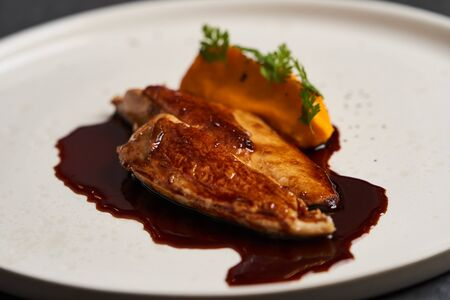 Sous vide chicken breast with mashed young carrots and chicken jus, close-up