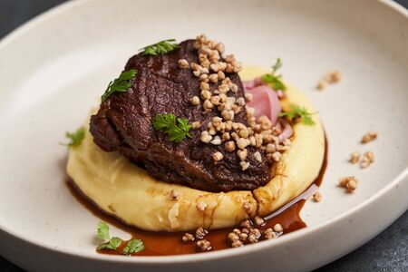 Stewed veal cheeks with mashed potatoes on a white plate, close-up. Luxury restaurant dish Stewed veal cheeks