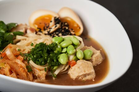 Asian noodles soup, ramen with chicken, tofu, vegetables and egg, close-up. Ramen noodle soup with chicken, shiitake mushroms and egg in a white bowl, top view.