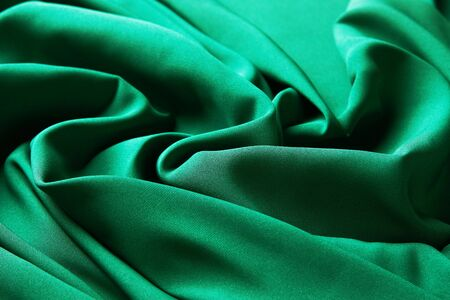 Green emerald color silk fabric background, top view. Smooth elegant green silk or satin luxury cloth texture can use as abstract background with copy space