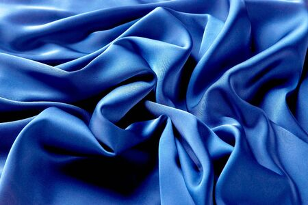Blue sapphire color silk fabric background, top view. Smooth elegant blue silk or satin luxury cloth texture can use as abstract background with copy space