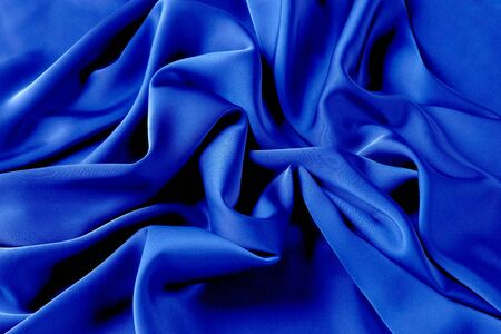 Blue sapphire color silk fabric background, top view. Smooth elegant blue silk or satin luxury cloth texture can use as abstract background with copy space Reklamní fotografie - 138466459