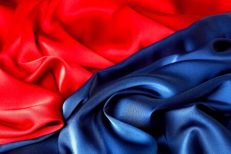 Red and blue color silk fabric background, top view. Smooth elegant blue and red silk or satin luxury cloth texture can use as abstract background with copy space