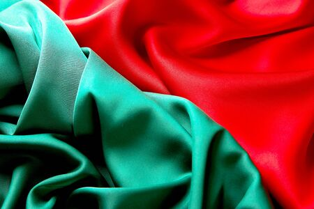 Red and green color silk fabric background, top view. Smooth elegant green and red silk or satin luxury cloth texture can use as abstract background with copy space