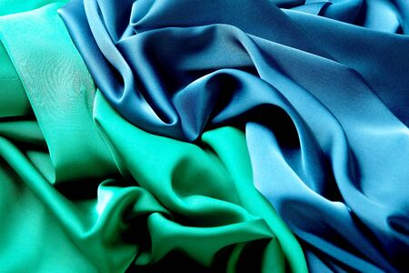 Blue and green color silk fabric background, top view. Smooth elegant green and blue silk or satin luxury cloth texture can use as abstract background with copy space