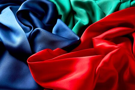 Blue green and red color silk fabric background, top view. Smooth elegant green blue and red silk or satin luxury cloth texture can use as colorful background with copy space Reklamní fotografie