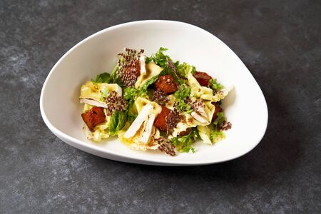 Baked Pumpkin salad with baked cheese, parsley herbs, white cabbage leaves, seeds. Healthy Pumpkin salad on a white plate on dark table background with copy space, close-up 写真素材