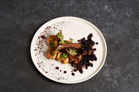 Lamb ribs with baked potatoes on a white plate, close-up. Barbecued lamb ribs with potatoes and blueberries sauce. Luxury restaurant menu food