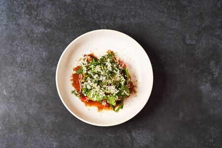 Healthy vegetable salad with grated cheese, close-up. Fresh vegetable salad in a white plate on dark table background with copy space. Healthy vegetarian food