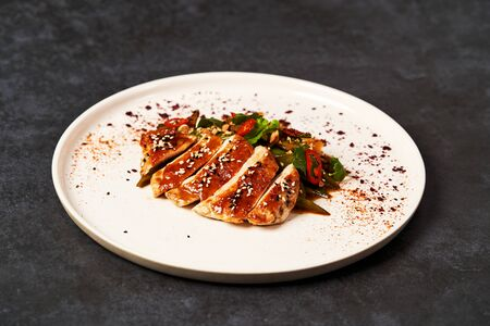 Spicy chicken breast with minted green beans, close-up. Grilled chicken fillet and baked green peppers on a white plate on gray table background with copy space. 写真素材