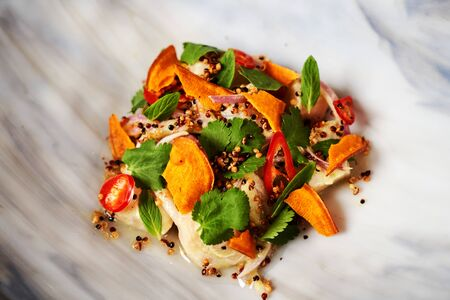 Healthy diet food - salted fish fillet, paprika, parsley herbs, fresh onion and spices. Vegetarian vegetable salad with fresh fish fillet. Luxury restaurant dish served on white plate on grey table