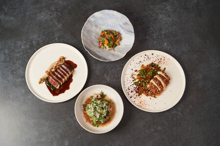 Set of various plates of food on a gray table background with copy space. Assorted food set served on restaurant table. Variety of Healthy diet food
