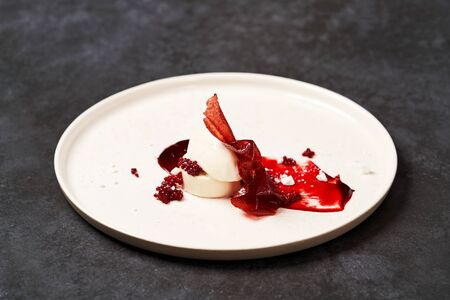Raspberry Sorbet on a white plate, close-up. Raspberry ice cream with sweet syrup on gray table background with copy space