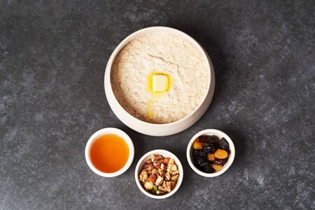 Healthy breakfast - milk rice porridge in a white plate on grey table background, close-up. Rice porridge with milk, raisins, honey and nuts in a bowl. Reklamní fotografie
