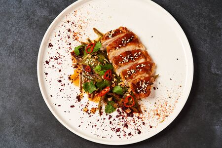 Spicy chicken breast with minted green beans, close-up. Grilled chicken fillet and baked green peppers on a white plate on gray table background with copy space
