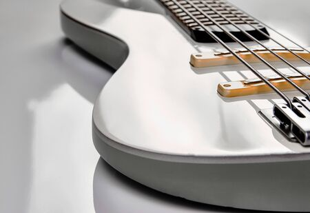 White Electric Bass Guitar strings, close-up. White bass guitar details on a white background with copy space.