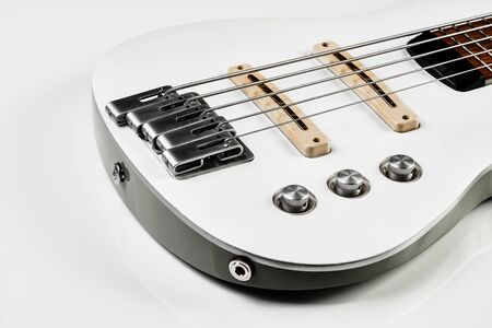 White bass guitar details on a white background with copy space. White Electric Bass Guitar strings, close-up